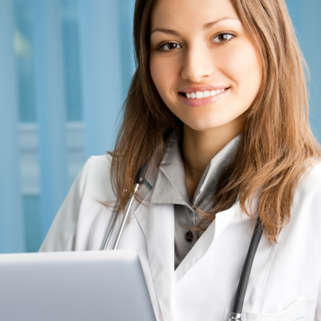 Portrait of cheerful female doctor working with laptop at office Stock Photo - 18658631