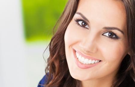 sonrisa: Retrato de joven y bella mujer sonriendo feliz, al aire libre, con copyspace Foto de archivo