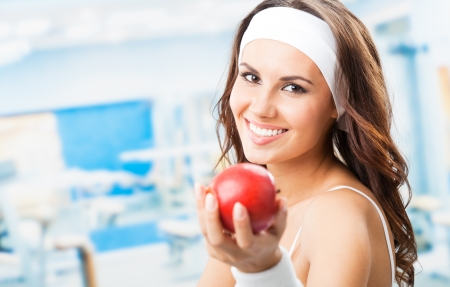 Cheerful young beautiful woman with red apple, at fitness center or gym, with copyspace photo