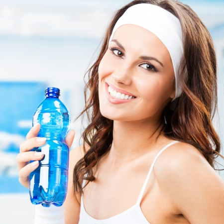 Portrait of cheerful young attractive woman with bottle of water, at fitness club or gym photo
