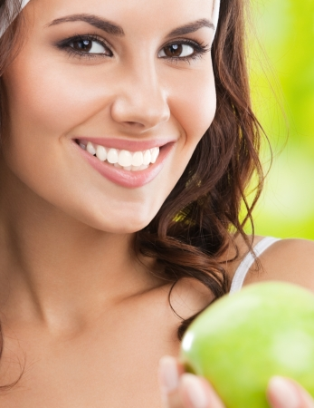 Portrait of happy smiling young beautiful woman in fitness wear with apple, outdoors photo