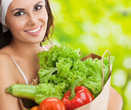 Portrait of happy smiling young beautiful woman in fitness wear holding grocery shopping bag with healthy vegetarian food, outdoors photo