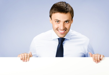 message board: Portrait of happy smiling young business man showing blank signboard, over violet background