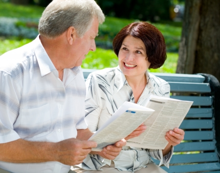 Happy smiling attractive senior couple reading together, outdoors photo