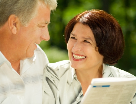 Heureux couple attrayant senior souriant à lire ensemble, à l'extérieur