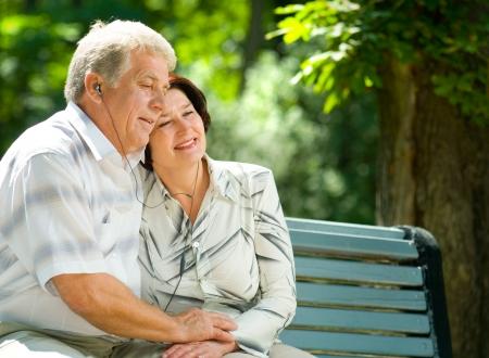 Happy couple gai écouter de la musique ou un livre audio dans le casque ou prier ensemble, en plein air Banque d'images