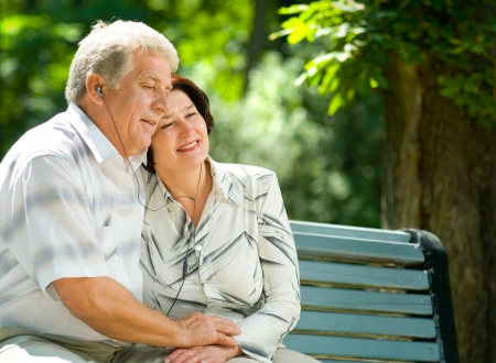 audio book: Happy smiling cheerful senior couple listening music or audio book in headset or praying together, outdoors Stock Photo