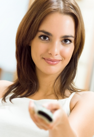 Portrait of young happy smiling woman watching TV at home photo
