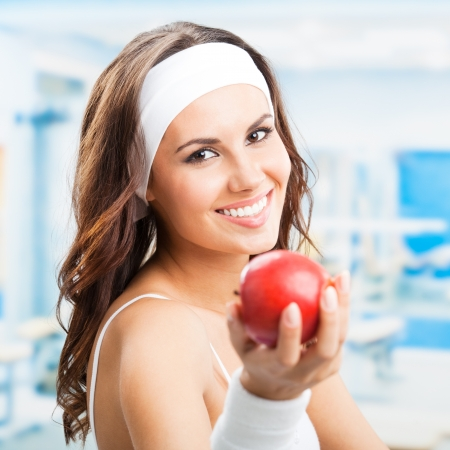 sportive: Cheerful young beautiful woman with red apple, at fitness center or gym