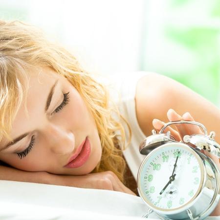 Blond schöne Frau mit Wecker auf dem Bett Standard-Bild - 19224268