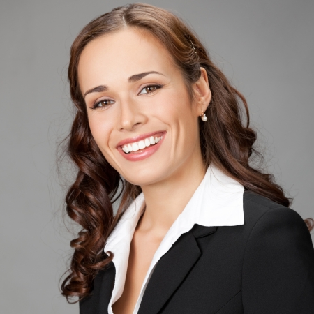 Portrait of happy smiling young business woman, over gray background photo