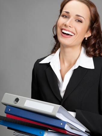Portrait of happy smiling young busy business woman with folders, over gray background Stock Photo - 19224300