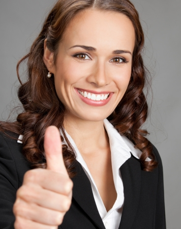 thumbs up gesture: Happy smiling cheerful young business woman showing thumbs up gesture, over grey background