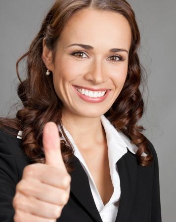 Heureux joyeux jeune femme d'affaires souriante montrant thumbs up geste, sur fond gris
