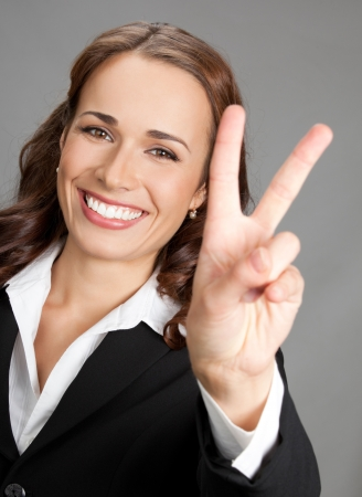 Happy smiling beautiful young business woman showing two fingers or victory gesture, over gray background Stock Photo - 19204007