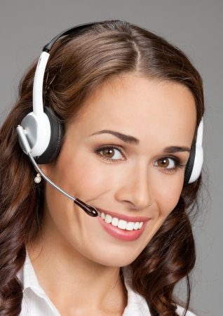 Portrait of happy smiling cheerful customer support phone operator in headset, over gray background Stock Photo - 19224359