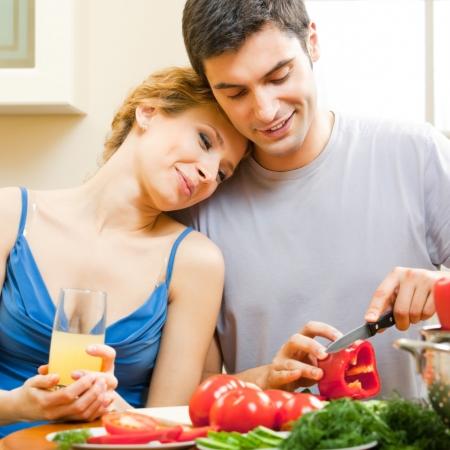 Cheerful young cooking couple prepairing vegetarian salad at home photo