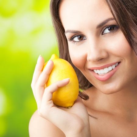 Jeune femme souriante heureuse avec du citron, à l'extérieur