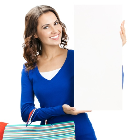 Portrait of young happy smiling woman with shopping bags, showing blank signboard or copyspace for slogan or text, isolated over white background photo