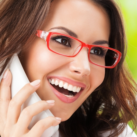 Portrait of happy smiling cheerful beautiful young business woman or support phone worker, at office Stock Photo - 19359146