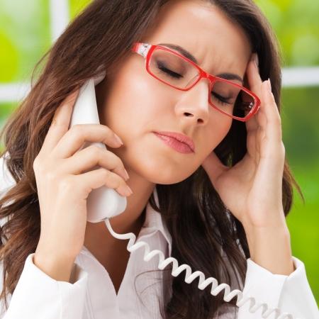 sick: Pensar, cansado o enfermo con dolor de cabeza Mujer de negocios con el tel�fono en la oficina