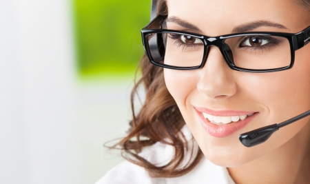 Portrait of happy smiling cheerful beautiful young support phone operator in headset, with copyspace Stock Photo - 19359149
