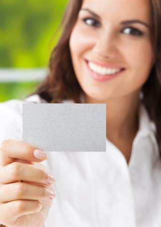 invitando: Feliz sonriente mujer de negocios que muestra la tarjeta de presentación en blanco, en la oficina. Centrarse en la tarjeta.