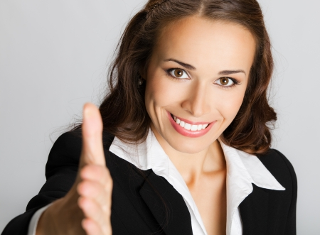 Portrait of young cheerful beautiful business woman giving hand for handshake, over gray background photo