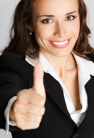 Happy smiling business woman showing thumbs up gesture, over gray background photo