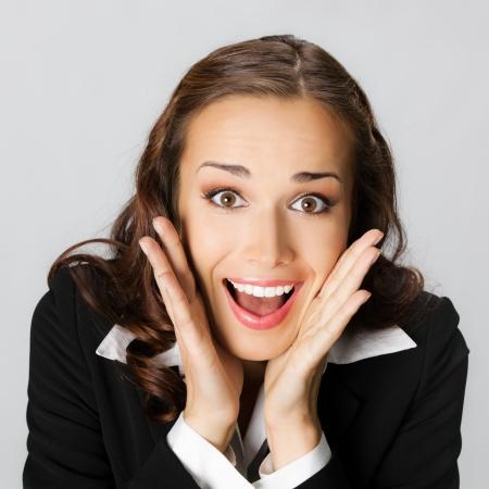 �tonnement: Portrait de jeune femme heureuse d'affaires sourire �tonn�, sur fond gris