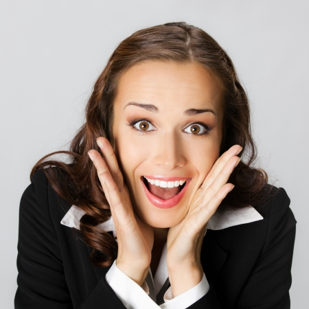 Portrait of young happy smiling surprised business woman, over gray background