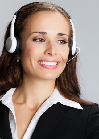 Portrait of happy smiling cheerful customer support phone operator in headset pointing at something, over gray background Stock Photo - 19459532