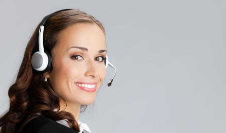 Portrait de l'heureux opérateur de support sourire à la clientèle gaie de téléphone dans le casque, sur fond gris, avec atelier