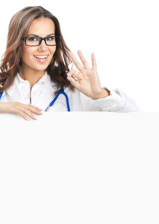 Portrait of happy smiling young female doctor showing blank signboard, with okay gesture, isolated over white background photo
