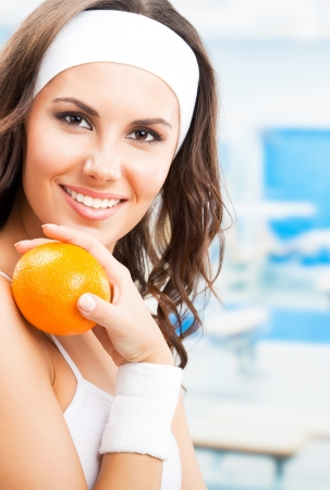 Cheerful young beautiful woman with orange, at fitness center or gym photo