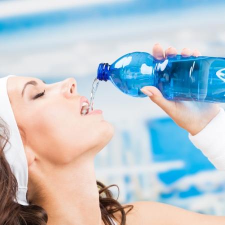girl drinking water: Portrait of cheerful young attractive woman drinking water, at fitness club or gym