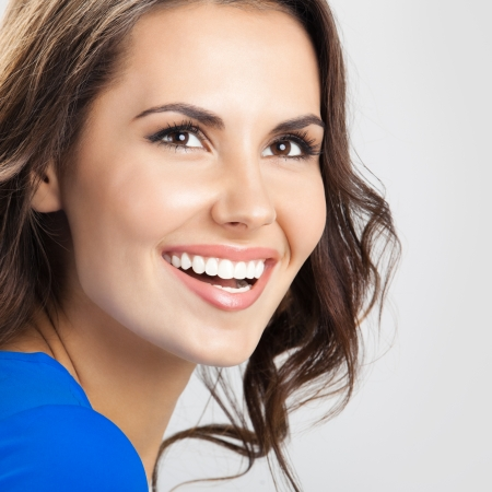 beautiful smile: Portrait of young cheerful smiling woman, over grey background