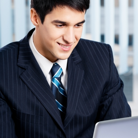 training consultant: Successful happy smiling businessman working with laptop at office
