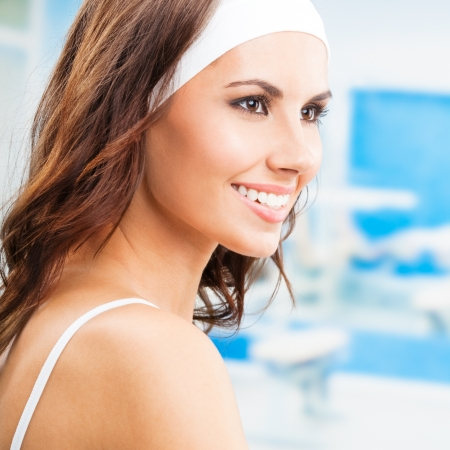 fitness club: Portrait of young cheerful smiling woman at fitness club or gym