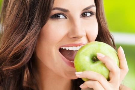 Portrait de jeune femme mangeant la pomme verte, en plein air