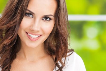 Portrait de la belle jeune femme souriante, ? l'ext?rieur, avec atelier