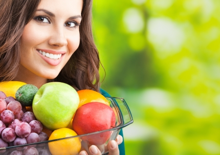 1 woman only: Young happy smiling woman with plate of fruits, outdoors, with copyspace for text or slogan. Stock Photo