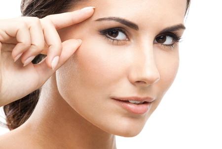 donna pensiero: Ritratto di felice sorridente bella giovane donna di toccare la pelle o applicare la crema, isolato su sfondo bianco
