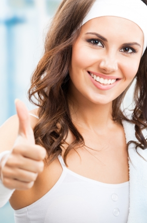 Portrait of cheerful young attractive woman showing thumbs up gesture, at fitness club or gym