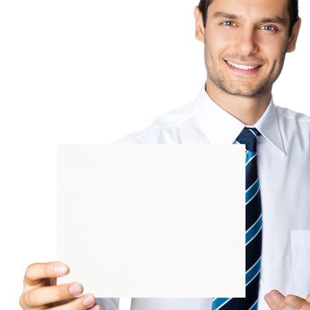 slogan: Feliz sonriente hombre de negocios joven que muestra letrero en blanco, aislados sobre fondo blanco Foto de archivo