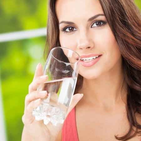 Portrait de jeune femme de boire de l'eau, en plein air