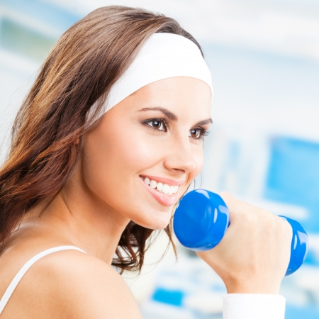 fitness center: Cheerful woman in fitness wear exercising with dumbbell, at fitness center or gym