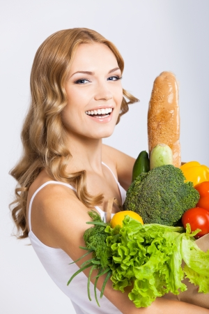 Portrait of happy smiling young beautiful woman holding grocery shopping bag with healthy vegetarian raw food, over gray background photo