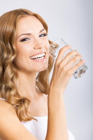 Portrait de jeune femme souriante eau potable heureux, sur fond gris