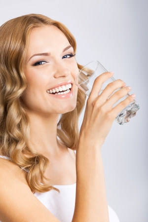 blondy: Portrait of young happy smiling woman drinking water, over gray background